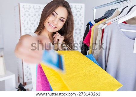 Happy woman in shop with a credit card in a hand - stock photo