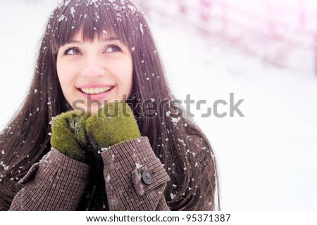 Happy woman in snow looking upwards - stock photo