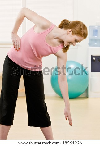 Happy woman in sportswear working out in health club