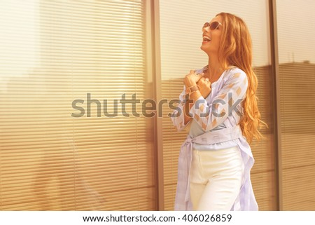 Happy woman in sunglasses laughing and looking up near office building. Long-haired girl in blue coat enjoying her daytime. - stock photo