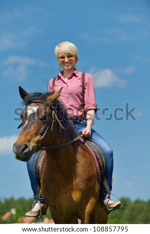 happy woman in sunglasses sitting on horse farm animal outdoors with blue sky in background