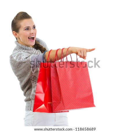 Happy woman in sweater with shopping bags pointing on copy space - stock photo