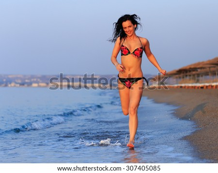 Happy woman in swimsuit running on the beach at sunrise