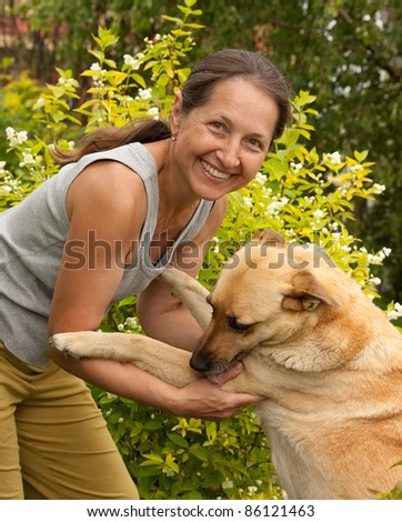 Happy woman in the garden playing with her dog - stock photo
