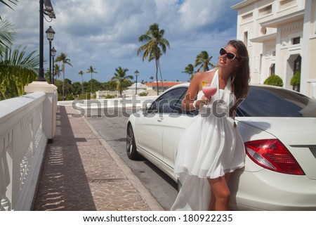 Happy woman in the luxury white car with cocktail at Valentine's day. Beautiful rich brunette woman smiling portrait. Summer vacation. - stock photo