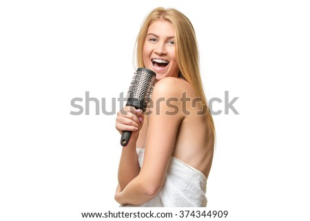 Happy woman in towel singing using comb   - stock photo