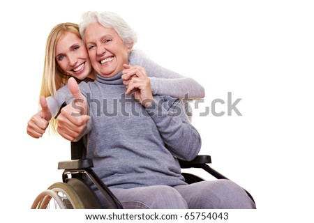 Happy woman in wheelchair with granddaughter holding her thumbs up - stock photo