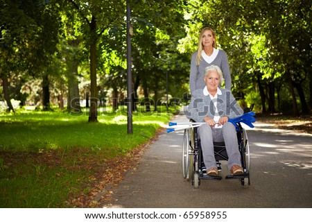 Happy woman in wheelchair with nurse in nature - stock photo