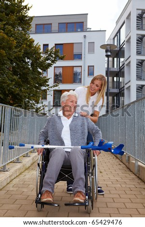 Happy woman in wheelchair with nurse on a ramp - stock photo