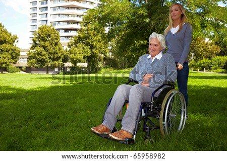 Happy woman in wheelchair with young woman in nature - stock photo