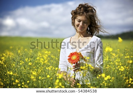 Happy woman in white dress holding red flowers in yellow rapeseed field. - stock photo