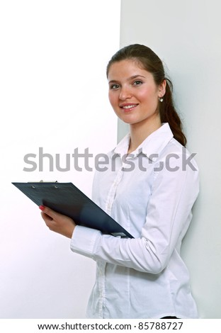 Happy woman in white shirt with clipboard standing against wall isolated - stock photo