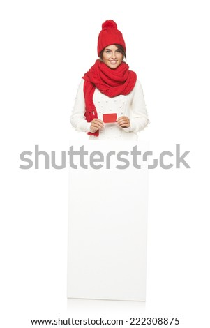 Happy woman in winter outerwear standing in full length with white banner and showing blank credit card, at studio over white background - stock photo