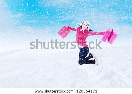Happy woman in winter outfit jumping with shopping bags outdoor - stock photo