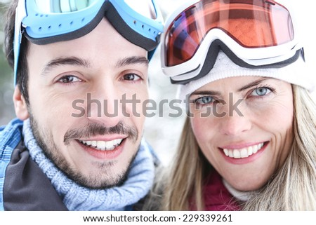 Happy woman in winter with ski goggles on a ski trip holding poles - stock photo