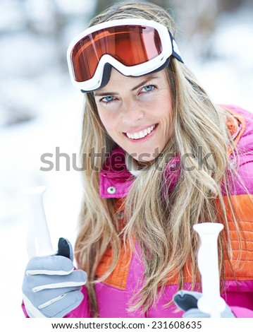 Happy woman in winter with ski googles on a ski trip holding poles - stock photo