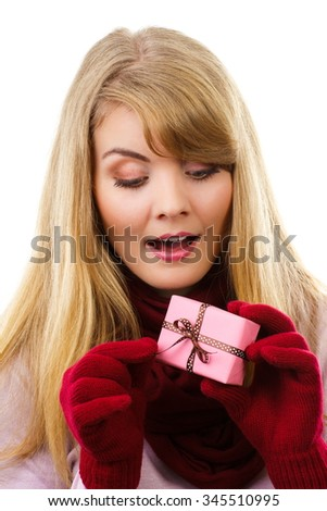 Happy woman in woolen shawl and gloves unwrapping gift for Christmas, valentine, birthday or other celebration, christmas time, white background - stock photo