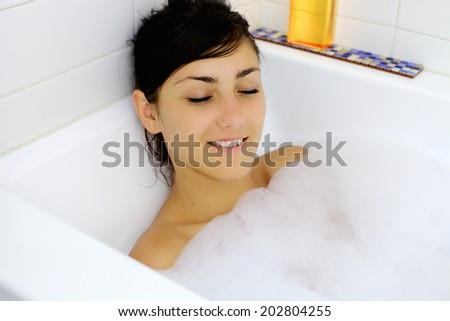 Happy woman inside bath tub having a good time - stock photo