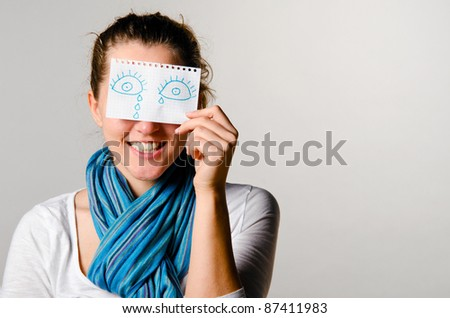 happy woman is holding paper with drawn tears - stock photo
