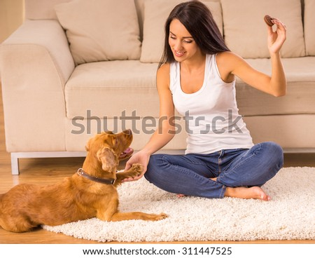 Happy woman is playing with a dog and feeding him sitting on the floor at home. - stock photo