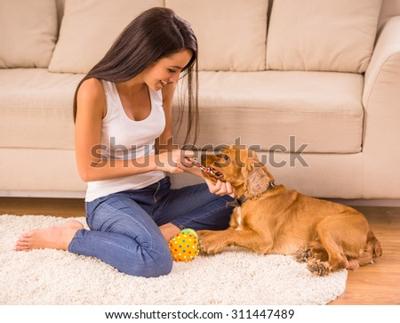 Happy woman is playing with a dog sitting on the floor at home. - stock photo