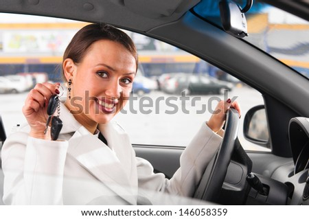 happy woman is showing keys of her new car - stock photo