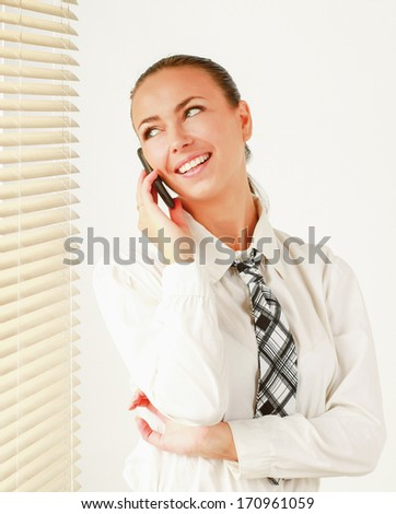 Happy woman is standing in the office near window and talking on phone