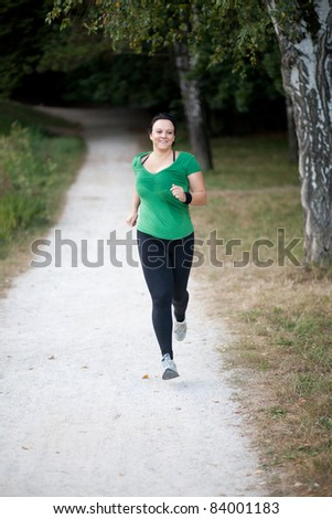 Happy woman jogging in a park/forrest to loose weight - stock photo