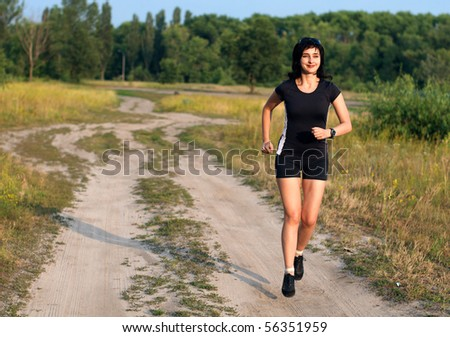 Happy woman jogging outdoors in summer - stock photo