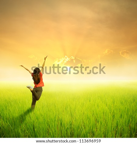 Happy woman jump in green rice fields and sunset