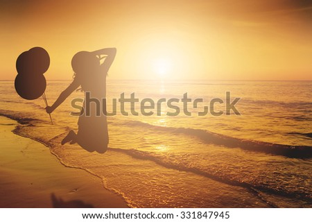 Happy Woman Jumping and holding balloons in Sea beach Sunset silhouette.Copy space - stock photo