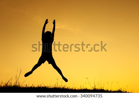 Happy woman jumping and sunset silhouette with copy space. - stock photo