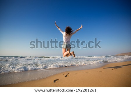 Happy woman jumping at the beach. Summer vacation concept - stock photo