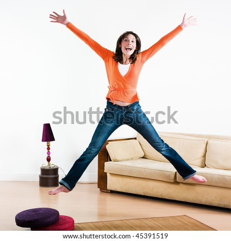 happy woman jumping in a living room - stock photo