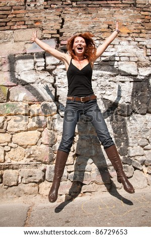 happy woman jumping in front the wall - stock photo