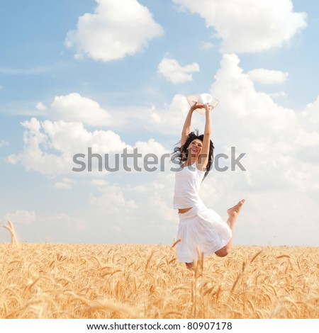 Happy woman jumping in golden wheat - stock photo