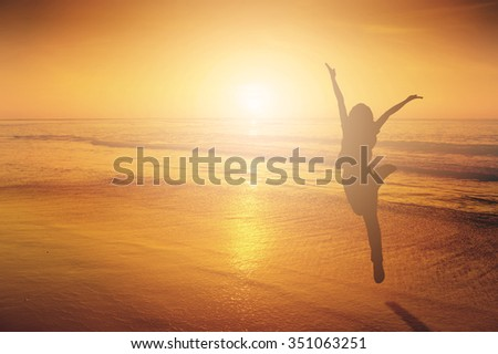Happy Woman Jumping in Sea beach Sunset silhouette.Copy space - stock photo