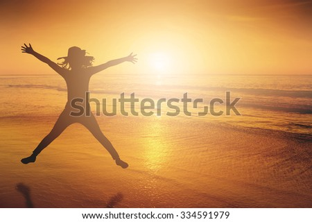 Happy Woman Jumping in Sea beach Sunset silhouette.Holiday vacation concept Copy space - stock photo