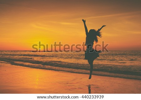 Happy Woman Jumping in Sea Sunset,summer vacation concept.Vintage tone. - stock photo