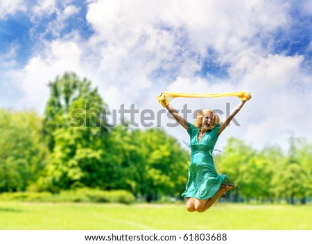 Happy woman jumping in the park. - stock photo