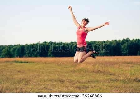 Happy woman jumping in yellow field