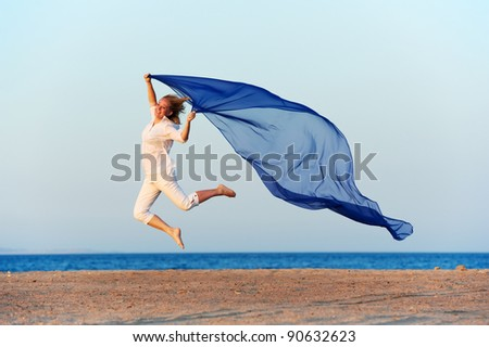 Happy woman jumping on sea beach with blue flying silk cloth - stock photo
