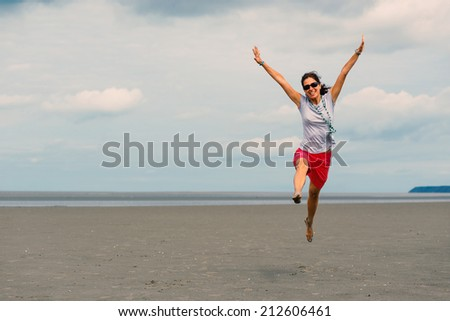 Happy woman jumping on the beach in front of Mont Saint Michel ancient village. Normandy, France.