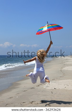 Happy woman jumping on the beach with umbrella - stock photo