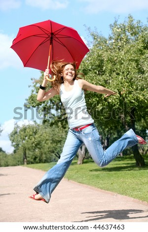happy woman jumping with a red umbrella in the garden - stock photo