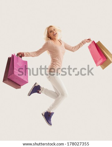 Happy woman jumping with shopping bags. - stock photo