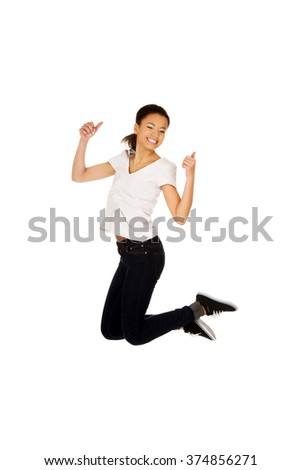 Happy woman jumping with thumbs up. - stock photo