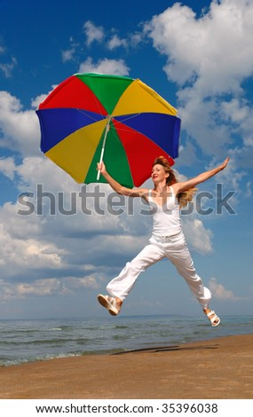 Happy woman jumps with umbrella