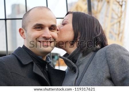 Happy woman kissing her smiling boyfriend on his cheek - stock photo