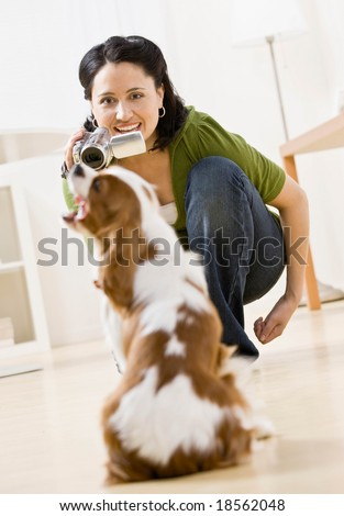 Happy woman kneeling and making video of pet dog with video camera - stock photo
